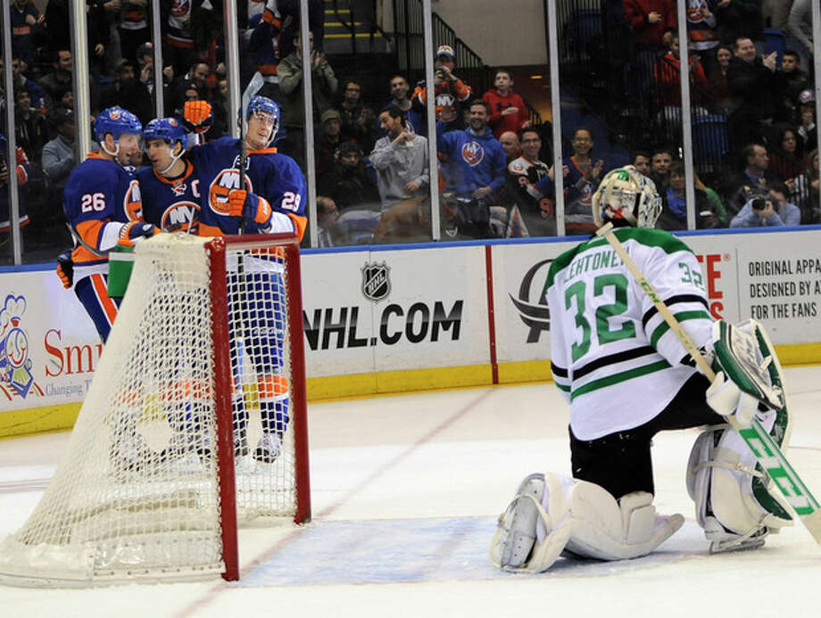 New York Islanders' Thomas Vanek (26), John Tavares (91) and Brock Nelson (29) celebrate a goal scored by Tavares against Dallas Stars goalie Kari Lehtonen (32) in the second period of an NHL hockey game on Monday, Jan. 6, 2014, in Uniondale, N.Y. (AP Photo/Kathy Kmonicek) / FR170189 AP