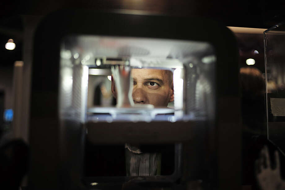 Ian Schick watches a plastic hand being printed in a 3D printer at the 3D Systems booth at the International CES, Wednesday, Jan. 7, 2015, in Las Vegas. (AP Photo/Jae C. Hong)
