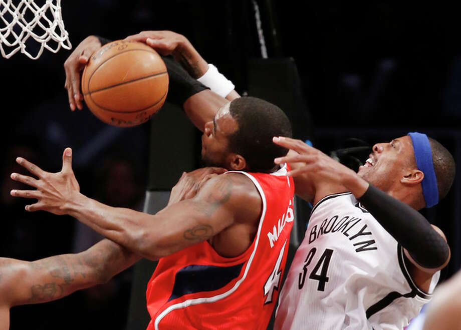 Brooklyn Nets forward Paul Pierce (34) defends Atlanta Hawks forward Paul Millsap (4) in the first half of their NBA basketball game at the Barclays Center, Monday, Jan. 6, 2014, in New York. (AP Photo/Kathy Willens) / AP