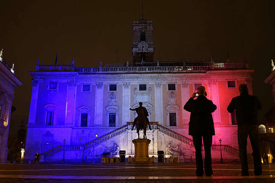 Rome's Capitol Hill, designed by Renaissance artist and architect Michelangelo Buonarroti, is lit with the colors of the French flag to express solidarity with those killed in an attack at the Paris offices of the satirical weekly Charlie Hebdo, Thursday, Jan. 8, 2015. Masked gunmen stormed the Paris offices of a weekly newspaper that caricatured the Prophet Muhammad, methodically killing 12 people Wednesday, including the editor in chief, before escaping in a car. (AP Photo/Andrew Medichini)