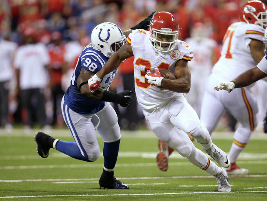 Kansas City Chiefs running back Knile Davis (34) runs from Indianapolis Colts outside linebacker Robert Mathis (98) during the first half of an NFL wild-card playoff football game Saturday, Jan. 4, 2014, in Indianapolis. (AP Photo/AJ Mast) / FR123854 AP