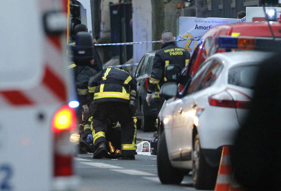 Rescue workers tend a victim after a shooting in Montrouge, south of Paris Thursday, Jan. 8, 2015. Two people were shot and gravely wounded at the southern edge of Paris, including a police officer, raising tensions a day after masked gunmen stormed the offices of a satirical newspaper and killed 12 people. (AP Photo/Christophe Ena)