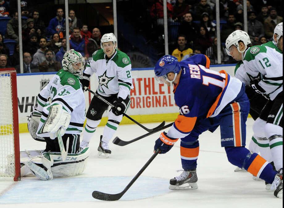 New York Islanders' Peter Regin (16) shoots the puck past Dallas Stars goalie Kari Lehtonen (32) to score in the second period of an NHL hockey game on Monday, Jan. 6, 2014, in Uniondale, N.Y. (AP Photo/Kathy Kmonicek) / FR170189 AP