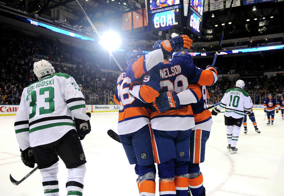 New York Islanders' Thomas Vanek (26), Brock Nelson (29) and John Tavares (91) celebrate Nelson's goal as Dallas Stars' Alex Goligoski (33) skates away in the third period of an NHL hockey game on Monday, Jan. 6, 2014, in Uniondale, N.Y. (AP Photo/Kathy Kmonicek) / FR170189 AP