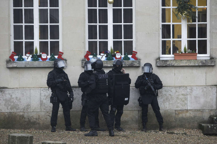 French riot officers patrol in Longpont, north of Paris, France, Thursday, Jan. 8, 2015. Scattered gunfire and explosions shook France on Thursday as its frightened yet defiant citizens held a day of mourning for 12 people slain at a Paris newspaper. French police hunted for the two heavily armed brothers suspected in the massacre to make sure they don't strike again. (AP Photo/Thibault Camus)