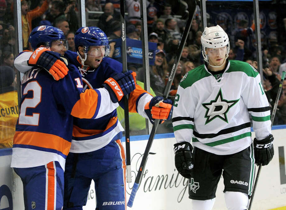 New York Islanders' Josh Bailey (12) hugs Peter Regin (16) as Dallas Stars' Alex Chiasson (12) reacts after Regin scored in the second period of an NHL hockey game on Monday, Jan. 6, 2014, in Uniondale, N.Y. (AP Photo/Kathy Kmonicek) / FR170189 AP