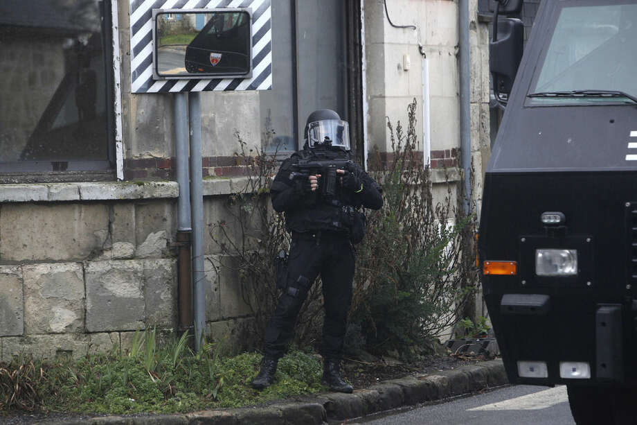 A French riot officer patrols in Longpont, north of Paris, France, Thursday, Jan. 8, 2015. Scattered gunfire and explosions shook France on Thursday as its frightened yet defiant citizens held a day of mourning for 12 people slain at a Paris newspaper. French police hunted for the two heavily armed brothers suspected in the massacre to make sure they don't strike again. (AP Photo/Thibault Camus)
