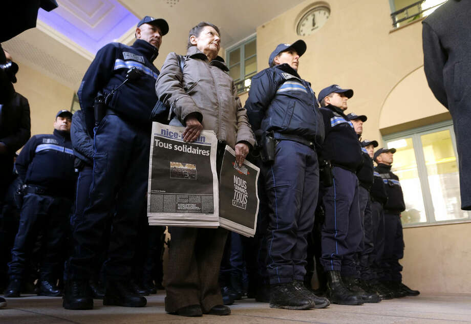 "A woman holding front pages of French newspapers reading ""All united"", left and ""We are all Charlie"", and Municipal police officers observe, a minute of silence for victims of the shooting at the satirical newspaper Charlie Hebdo, in Nice town hall, southeastern France Thursday, Jan. 8, 2015. With tensions high across Paris, French authorities focused Thursday on preventing new attacks and police hunted for two heavily armed brothers _ one with a history of jihadi ties _ in the methodical killing of 12 people at a satirical newspaper that caricatured the Prophet Muhammad.(AP Photo/Lionel Cironneau)"