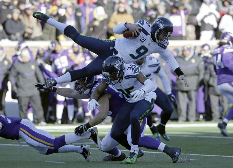 Seattle Seahawks punter Jon Ryan (9) jumps over Minnesota Vikings linebacker Casey Matthews (59) as he runs the ball during the first half of an NFL wild-card football game against the Minnesota Vikings, Sunday, Jan. 10, 2016, in Minneapolis. (AP Photo/Nam Y. Huh)