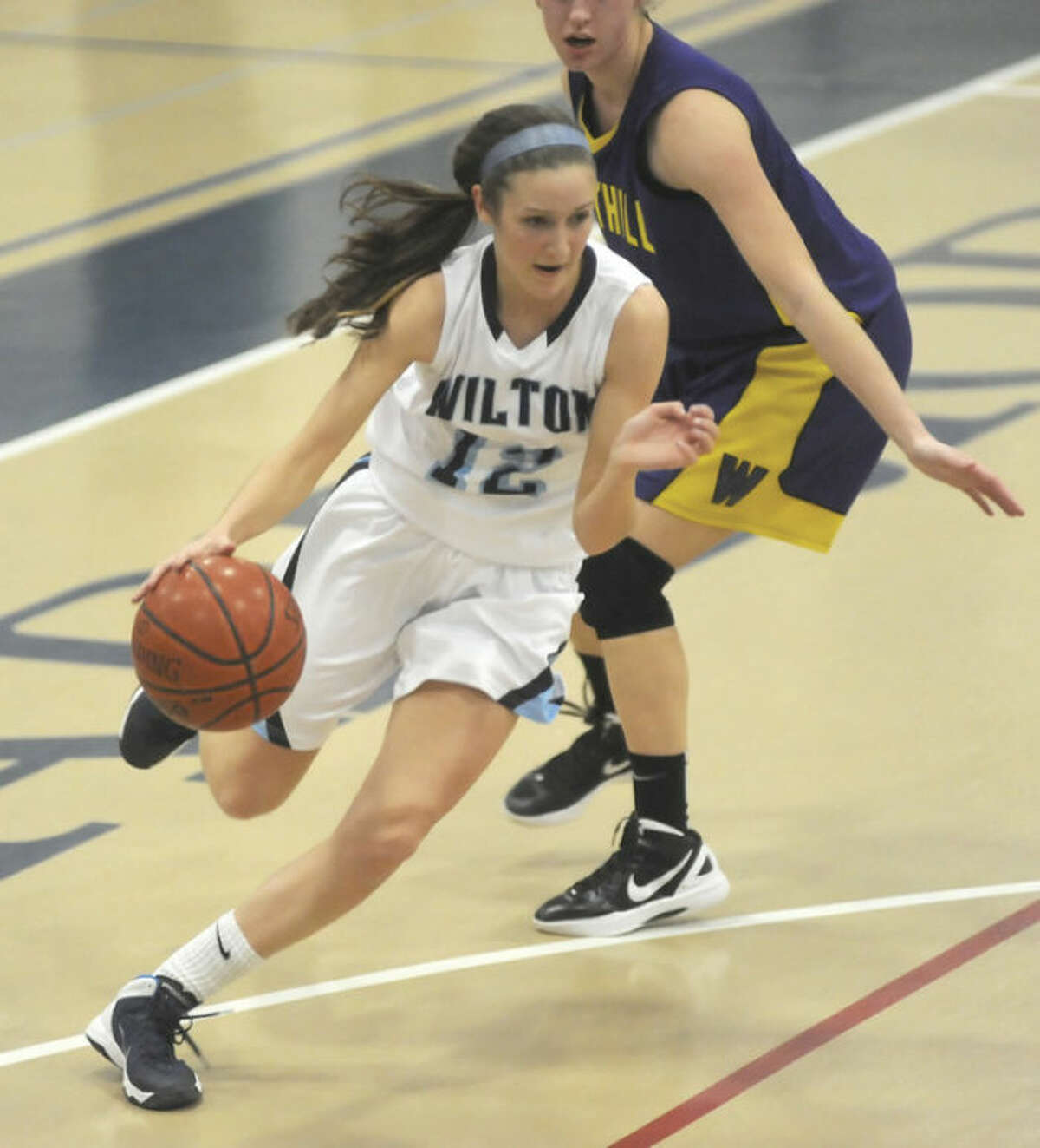 Hour photo/John Nash Wilton's Haley English drives past a Westhill defender on the way to the basket during Monday's game in Wilton.