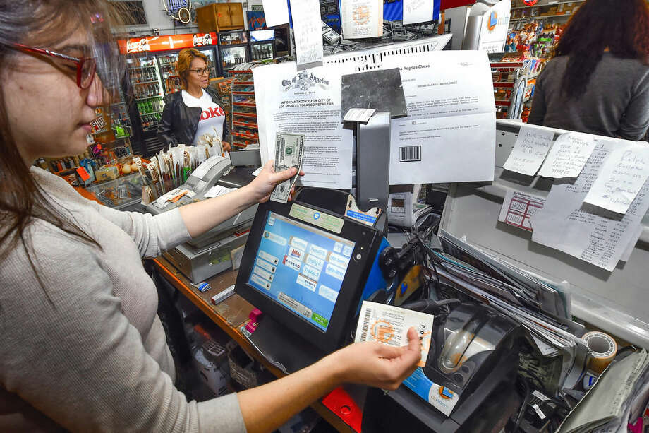 Jennifer Rawashdeh enters tickets as customers wait in line at the Eagle Market Store to buy Powerball lottery tickets in Sherman Oaks area of Los Angeles. on Saturday, Jan. 9, 2016. (AP Photo/Gus Ruelas)