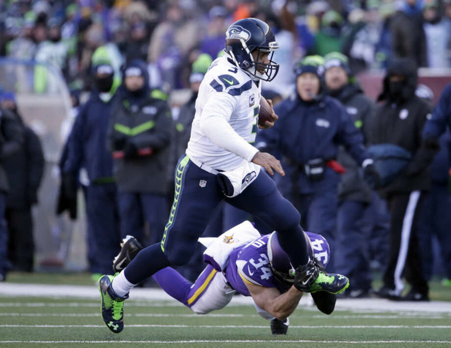 Seattle Seahawks quarterback Russell Wilson (3) runs the ball against Minnesota Vikings strong safety Andrew Sendejo (34) during the first half of an NFL wild-card football game, Sunday, Jan. 10, 2016, in Minneapolis. (AP Photo/Nam Y. Huh)