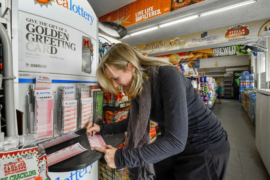 Emily Burnett marks her numbers at the Eagle Market Store as she prepares to buy Powerball lottery tickets in Los Angeles, Saturday, Jan. 9, 2016. Ticket sales for the multi-state Powerball lottery soared Saturday as people dreamed of winning the largest jackpot in U.S. history which grew by $100 million to hit $900 million just hours before Saturday night's drawing. (AP Photo/Gus Ruelas)