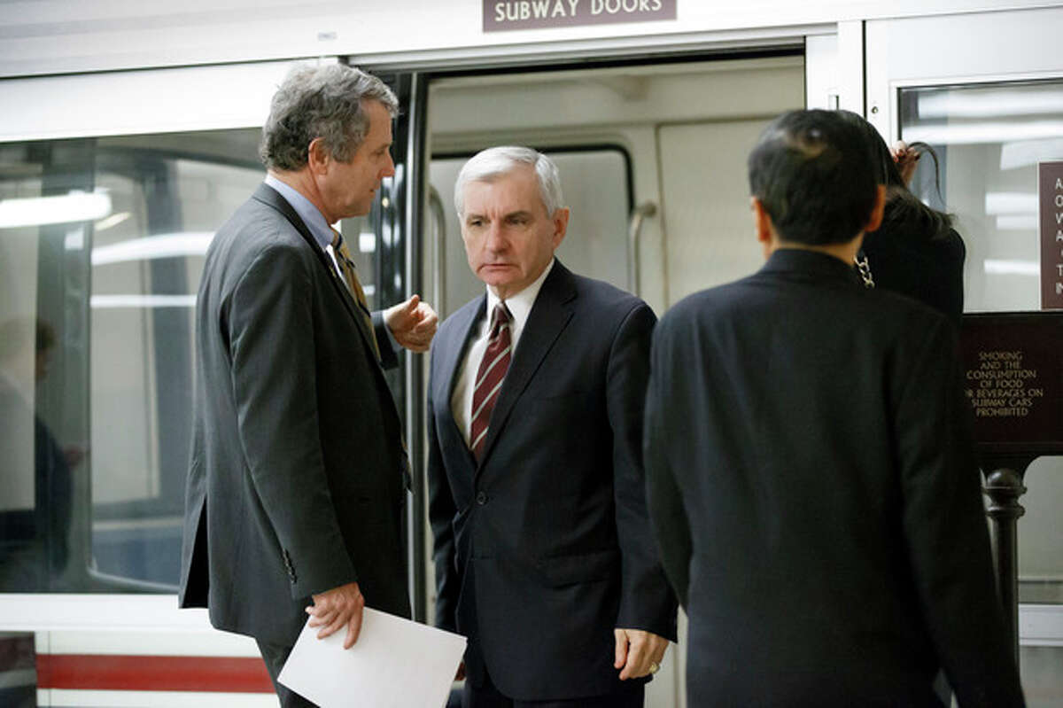 Sen. Jack Reed, D-R.I., right, and Sen. Sherrod Brown, D-Ohio, left, confer before a procedural vote in the Senate on a bill that would extend unemployment benefits, at the Capitol in Washington, Monday, Jan. 6, 2014. Benefits expired for many long-term unemployed Americans on Dec. 28 after lawmakers did not extend the program as part of a bipartisan budget agreement. Sen. Jack Reed, D-R.I., is leading the effort to reauthorize the benefits for three months nationwide, but Republicans are balking however have balked at the proposed extension without offsets for the $6.5 billion that it will cost. (AP Photo/J. Scott Applewhite)