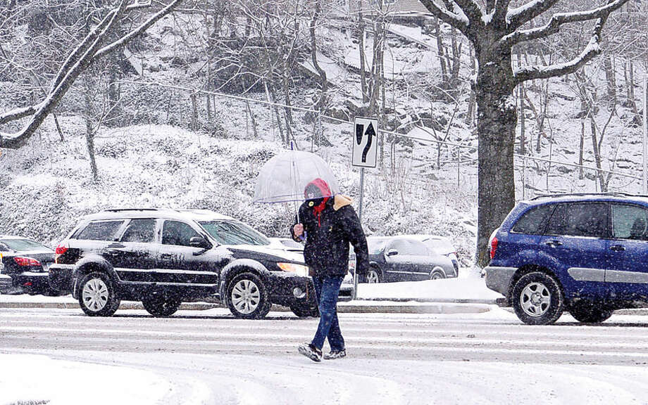 Hour photo / Erik Trautmann A pedestrian crosses Martin Luther King Jr Boulevard during the surprise snowfall Friday morning.