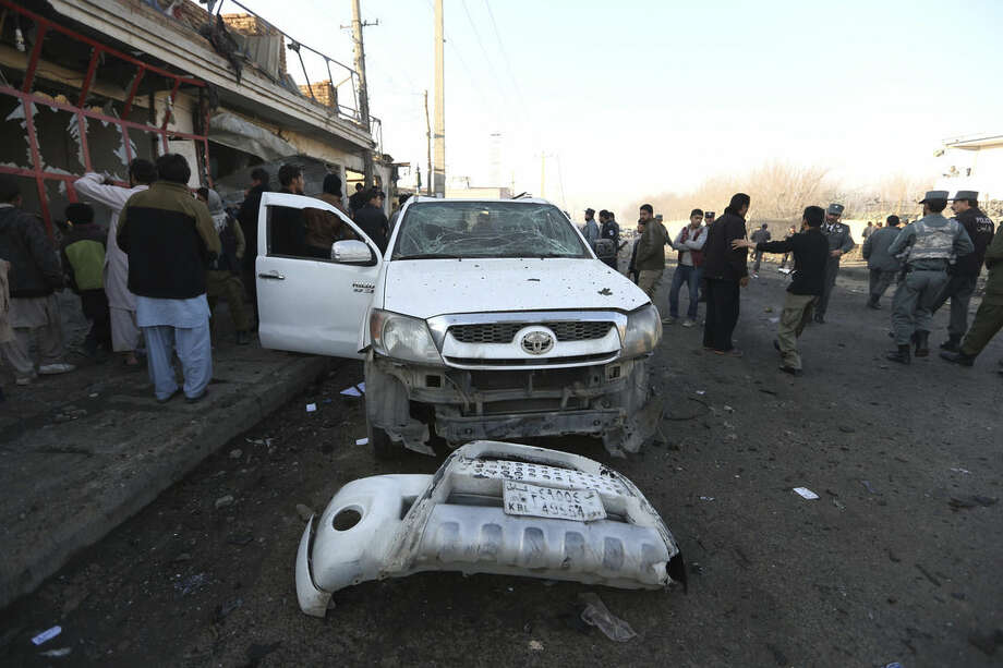 "FILE - In this Monday, Dec. 28, 2015, file photo, Afghan security forces inspect the site of a suicide car bomb attack near the Kabul airport in Kabul, Afghanistan. Afghan forces are struggling to man the front lines against a resurgent Taliban, in part because of untold numbers of ""ghost"" troops who are paid salaries but only exist on paper. (AP Photo/Rahmat Gul, File)"