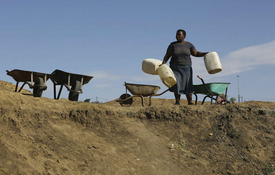 In this Thursday Jan. 7, 2016 photo, a woman arrives to collect stagnant rain water from an unfinished sewerage treatment tank, now used as a well, to do her laundry in Senekal, South Africa where taps and water sources have run dry. Senekal, a small town in South Africa's rural Free State province, is one of four regions declared disaster areas as a drought dries up South Africa's heartland _ along with much of eastern and southern Africa _ bringing with it failed crops and acute water shortages. (AP Photo/Denis Farrell)