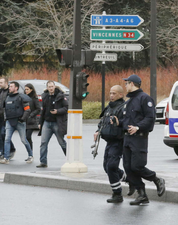 Police officers arrive at a hostage-taking situation at a kosher market in Paris, Friday Jan. 9, 2015. France's anti-terrorism prosecutor says a shooting and hostage-taking attack is underway at a kosher market on the eastern edge of Paris. A police official said there are multiple hostages and wounded at the scene. (AP Photo/Francois Mori)