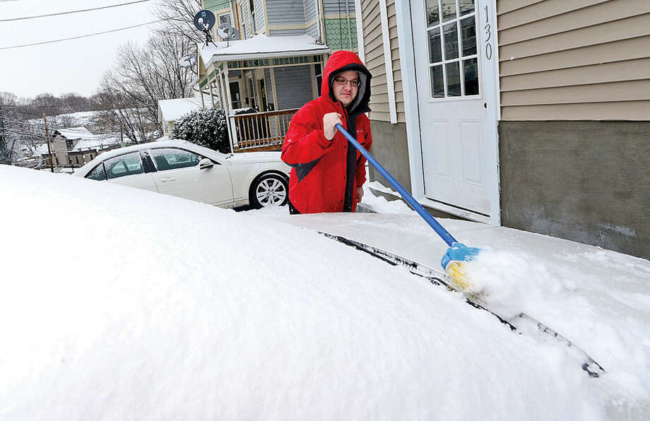 Hour photo / Erik Trautmann Norwalk resident Nick Kiriakidis cleans off his car after the surprise snowfall Friday morning.