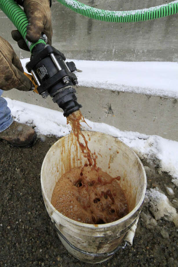 In a demonstration, a bucket is filled with beet juice at the Pennsylvania Department of Transportation's Butler, Pa., maintenance facility, Monday, Jan. 6, 2014. Because rock salt is largely ineffective below 16 degrees, road salt is mixed with additives, such as beet juice and cheese brine, to keep it working in temperatures as low as minus 25. (AP Photo/Gene J. Puskar)