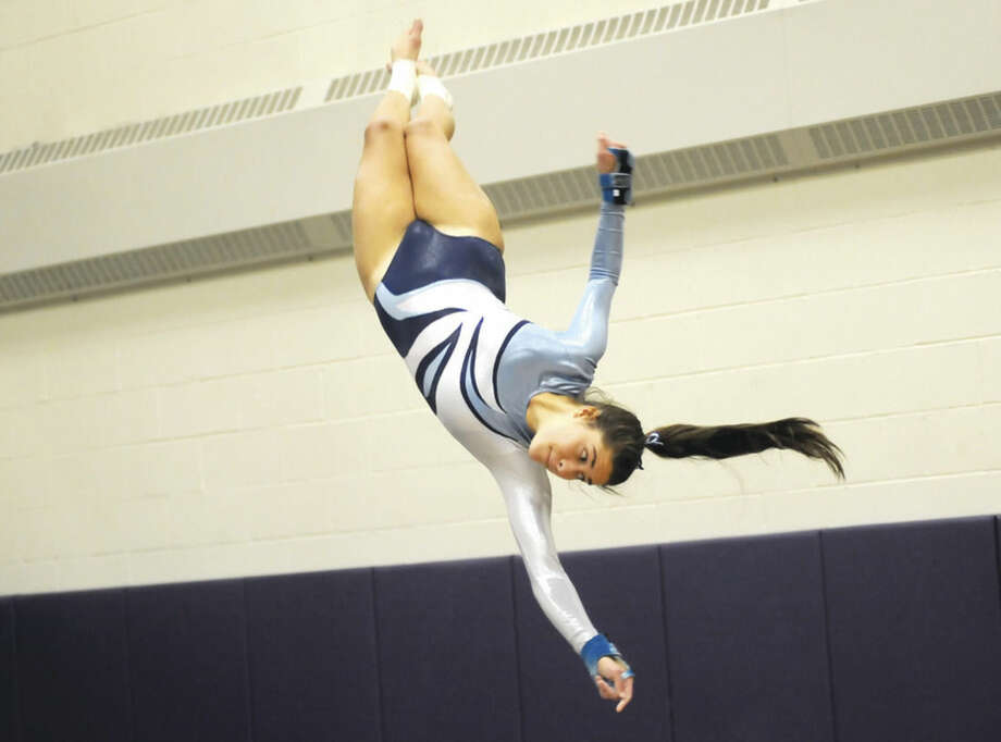 Hour photo/John NashWilton's Sara Posson flings herself through the air during the vault at Thursday's season-opening meet for the Warriors at Westhill High in Stamford. Wilton won the three-way meet by scoring 126.35 points.