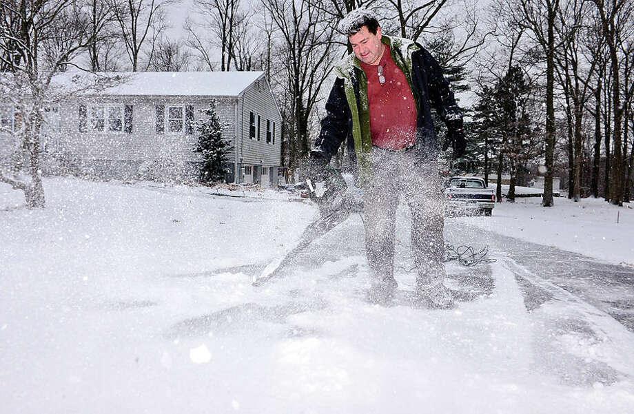 Hour photo / Erik Trautmann Norwalk resident Lou Montanari clean up his driveway after the surprise snowfall Friday morning.