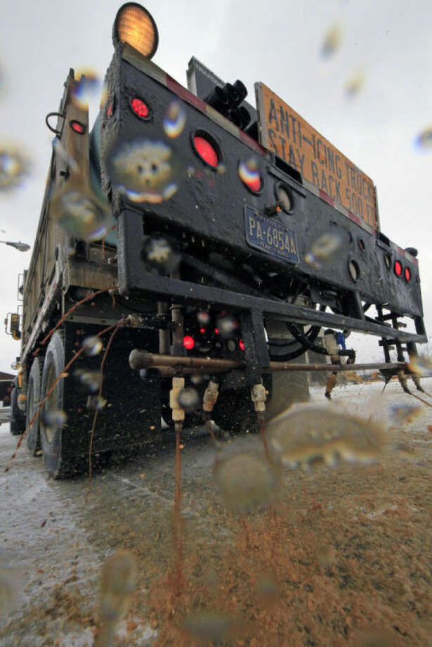 In a demonstration, a Pennsylvania Department of Transportation anti-icing truck sprays a de-icing cocktail of brine and beet juice on the driveway of PennDot's Butler, Pa., maintenance facility, Monday, Jan. 6, 2014. Because rock salt is largely ineffective below 16 degrees, additives, such as beet juice and cheese brine, can keep it working in temperatures as low as minus 25. (AP Photo/Gene J. Puskar)