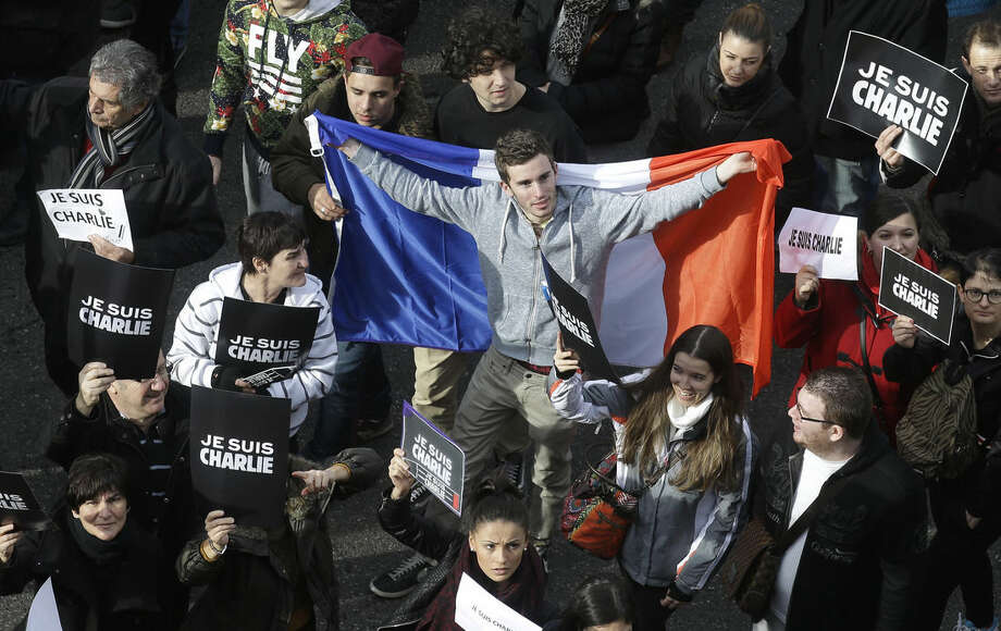 "A man holds a French flag during a silent walk for victims of the shooting at the satirical newspaper Charlie Hebdo, Saturday, Jan. 10, 2015, in Nice, southeastern France. The placards reads ""I am Charlie"". Ten journalists and two policemen were killed last Jan. 07 in a terrorist attack at the Charlie Hebdo headquarters in Paris. (AP Photo/Lionel Cironneau)"
