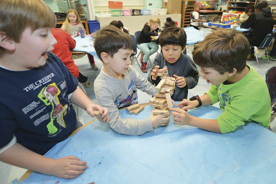 Hour Photo/Alex von Kleydorff L-R John Hood, Liam Cade, Brandon Stewart -Jones and Joshua Stewart- Jones play Jenga during the Norwalk YMCA after school program at Columbus Magnet School
