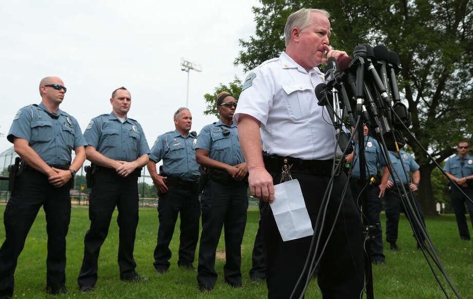 File-This Aug. 15, 2014, file photo shows Ferguson Police Chief Tom Jackson surrounded by his officers as he answers questions at a news conference in Forestwood Park. Interviews with several elected officials and newly released records show some of Missouri's top leaders tried to pressure Ferguson Police Chief Tom Jackson to resign after the fatal shooting of Michael Brown.Ferguson Mayor James Knowles III told The Associated Press Friday, Jan. 9, 2015, there were several meetings where pressure was applied. Jackson never resigned. (AP Photo/St. Louis Post-Dispatch, Robert Cohen, File)