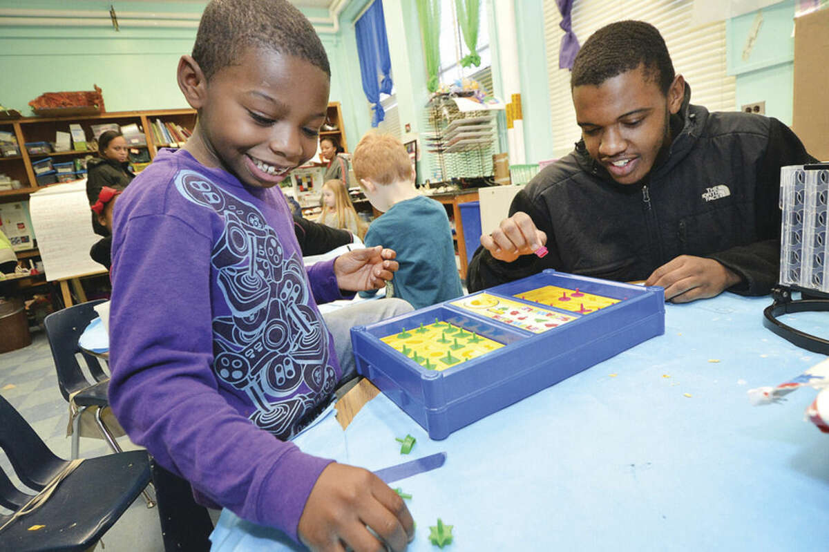 Hour Photo/Alex von Kleydorff 7yr old Josiah Lewis is on his way to a 'Scamble' win with After School Assistant Patrick Corley during Norwalk YMCA after school program at Columbus Magnet School