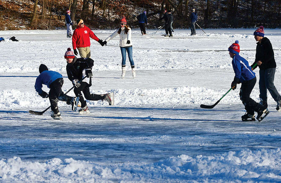 Hour photo / Erik Trautmann Local residents use the frozen Woods Pond Saturday to play hockey and figure skate.