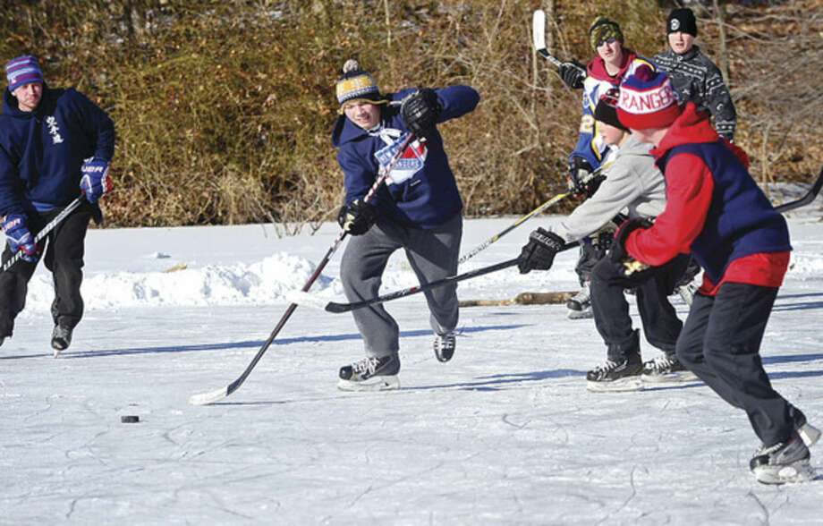 Hour photo / Erik Trautmann Local skaters including Matthew Cavanaugh and his friends use the frozen Woods Pond Saturday for a pick-up game of hockey.