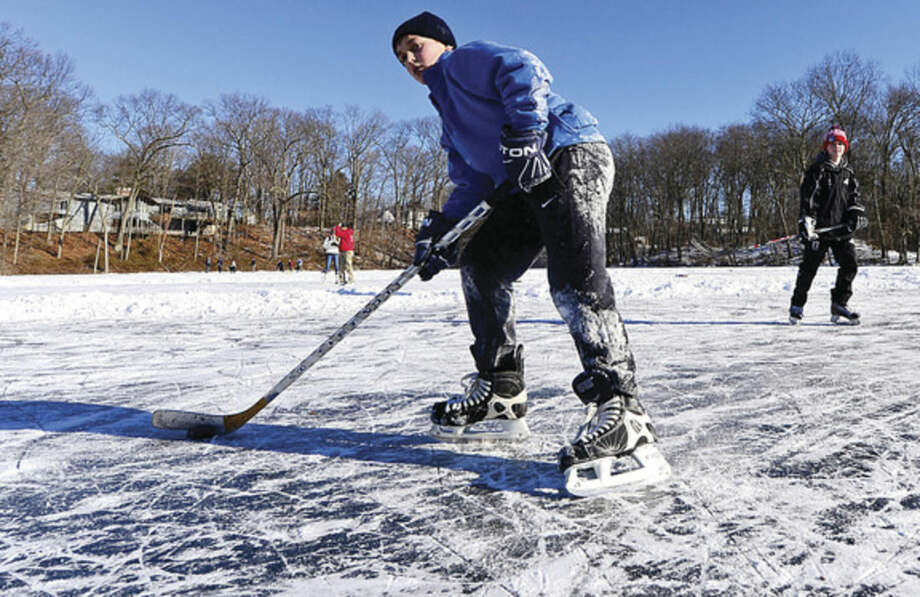 Hour photo / Erik Trautmann Local skaters including Patrick Coulter use the frozen Woods Pond Saturday to play hockey.