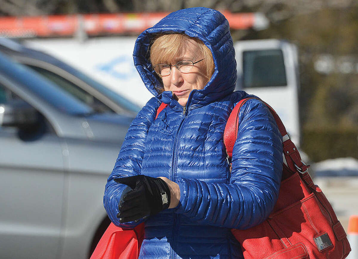 Susan Lauricella braces herself against the cold weather as she puts on gloves and heads to The Wilton Library during Tuesday's frigid weather.