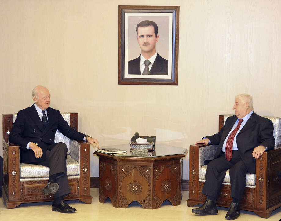 "In this photo released by the Syrian official news agency SANA, Syria's Foreign Minister Walid al-Moallem, second right, meets with U.N. Special Envoy for Syria Staffan de Mistura, second left, in Damascus, Syria, Saturday, Jan. 9, 2016. Syria is ready to attend peace talks later this month in Geneva but the government wants to see lists of the opposition groups who will attend and ensure that ""terrorist"" groups that will not, the country's foreign minister said Saturday according to SANA. (SANA via AP)"