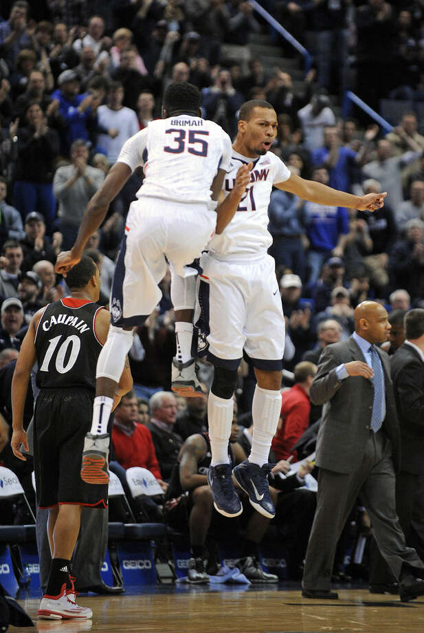 Connecticut's Omar Calhoun (21) and Amida Brimah (35) celebrate late in the second half of their 62-56 victory over Cincinnati in an NCAA college basketball game in Hartford, Conn., Saturday, Jan. 10, 2015. (AP Photo/Fred Beckham)