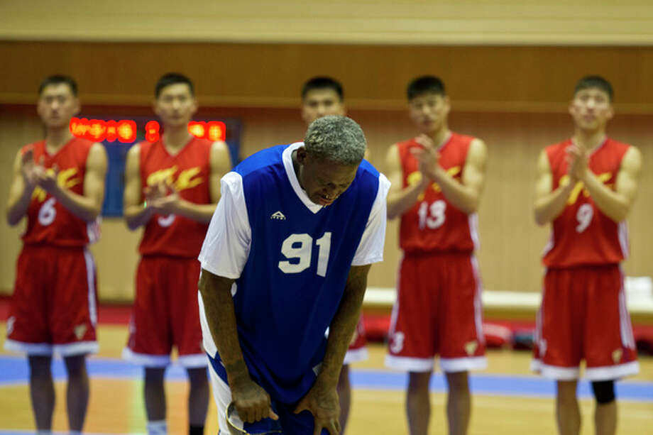 Dennis Rodman bows to North Korean leader Kim Jong Un, seated above in the stands, after singing Happy Birthday to Kim before an exhibition basketball game with U.S. and North Korean players at an indoor stadium in Pyongyang, North Korea on Wednesday, Jan. 8, 2014. (AP Photo/Kim Kwang Hyon) / AP