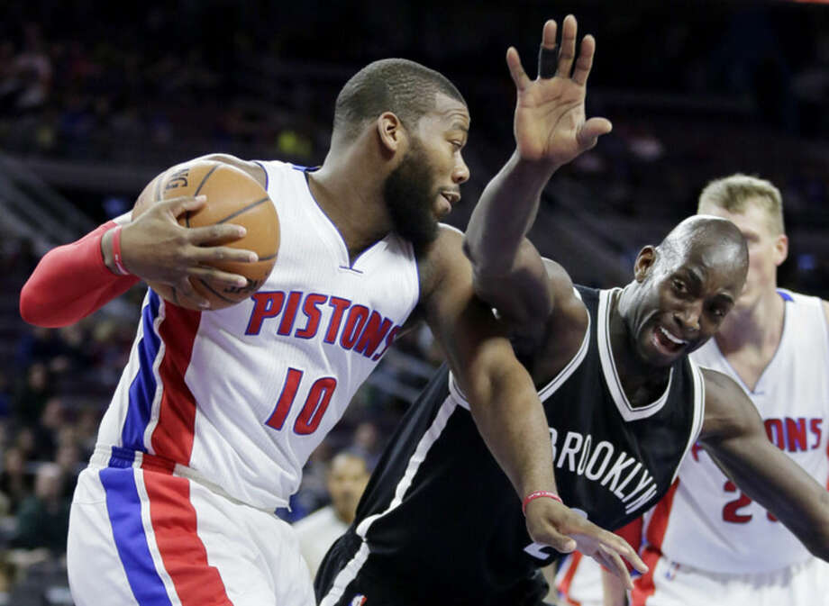 Brooklyn Nets' Kevin Garnett, front right, tries to swipe the ball from Detroit Pistons' Greg Monroe (10) during the first half of an NBA basketball game Saturday, Jan. 10, 2015, in Auburn Hills, Mich. (AP Photo/Duane Burleson)