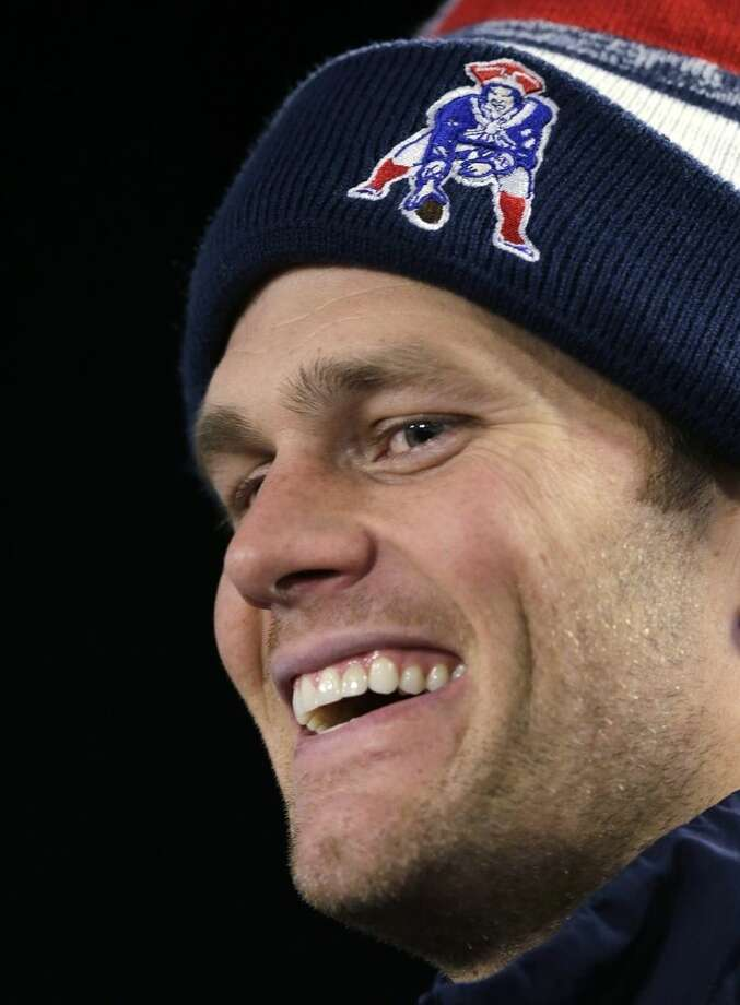 New England Patriots quarterback Tom Brady smiles during a news conference after an NFL football practice in Foxborough, Mass. , Tuesday, Jan. 6, 2015. The Patriots face the Baltimore Ravens in a divisional playoff on Saturday. (AP Photo/Charles Krupa)