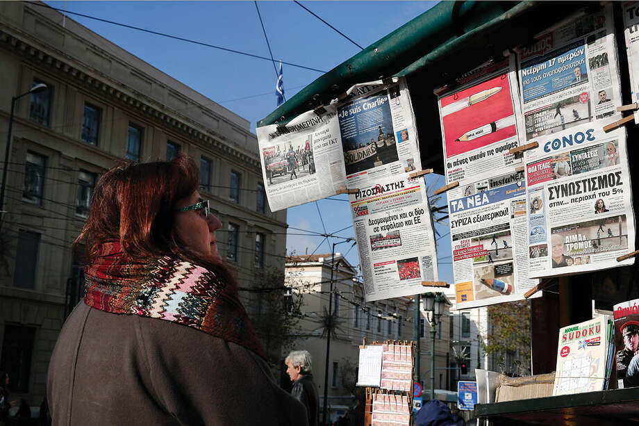 "A woman reads the front pages of newspapers hanging from a kiosk, following the Wednesday's attack of Charlie Hebdo newspaper, in Athens, on Thursday, Jan. 8, 2015. French police hunted Thursday for two heavily armed men _ one with a terrorism conviction and a history in jihadi networks _ in the methodical killing of 12 people at a satirical newspaper that caricatured the Prophet Muhammad. Banner headlines clockwise from the top-left read: ""The freedoms of Europe are targeted"", ""I am Charlie"" in French, ""Pens beat bullets"", ""Bullets in Paris, terror in Europe,"",""Blood and terror in the heart of Europe"", ""Horror in Paris the cold-blooded murder of freedom of speech."" The paper on bottom left does not have the issue on its front page. (AP Photo/Petros Giannakouris)"