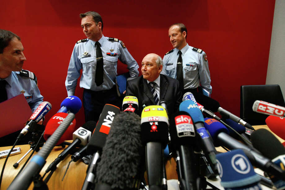 Albertville prosecutor Patrick Quincy, center, arrives with investigators for a press conference in the Albertville law court, French Alps, Wednesday Jan. 8, 2014. Two minutes of footage from a camera on Michael Schumacher's ski helmet showed the Formula One great was clearly skiing off a groomed trail when he lost his balance and crashed, leaving him with critical head injuries, investigators said Wednesday. The investigators said they have ruled out problems with his skis, trail conditions and signage. Although they would not estimate Schumacher's speed, they said it was not considered a significant factor in the Dec. 29 crash at the Meribel resort in the French Alps. (AP Photo/Claude Paris) / AP