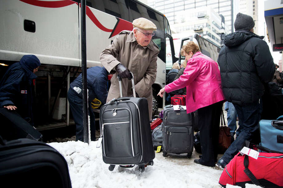 Passengers unload their luggage after arriving at Union Station after their Amtrak train from Los Angeles became stuck in snow drifts on Tuesday, Jan. 7, 2014, in Chicago. The severe weather forced hundreds of Amtrak passengers to spent the night onboard three trains stranded due to the snow in northern Illinois. (AP Photo/Andrew A. Nelles) / FR170974 AP