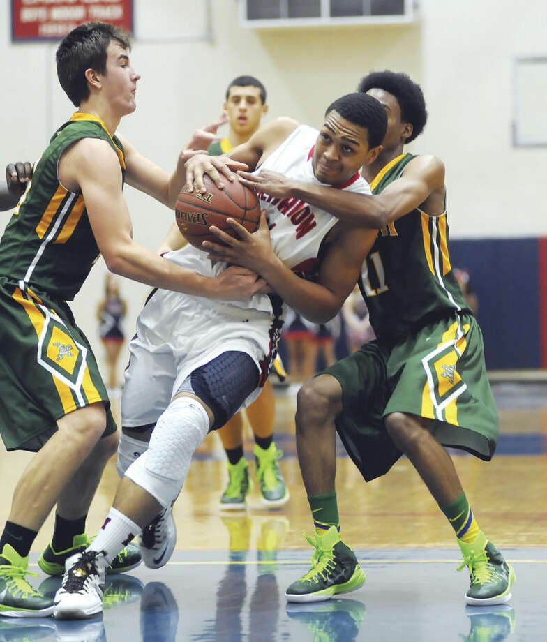 Hour photo/John NashBrien McMahon's Timmy Hinton Jr., center, is fouled by either one or two Trinity Catholic players during the first quarter of Friday's game at King-Kehoe Gym in Norwalk.