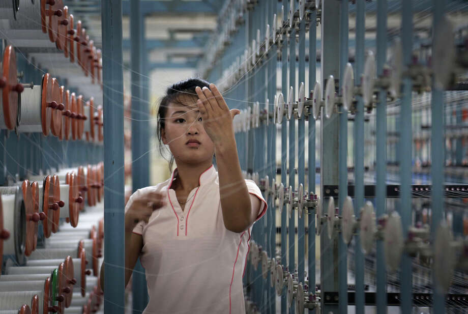 FILE - In this Thursday, July 31, 2014, file photo, a North Korean woman works at the Kim Jong Suk Pyongyang textile factory, in Pyongyang, North Korea. After ringing in the new year with claims of its first successful hydrogen bomb test, North Korea is now calling on the United States and the world community to accept it as a nuclear power, jettison the pursuit of punitive sanctions and allow it to focus on what it really wants: build up the nation's troubled economy.(AP Photo/Wong Maye-E, File)