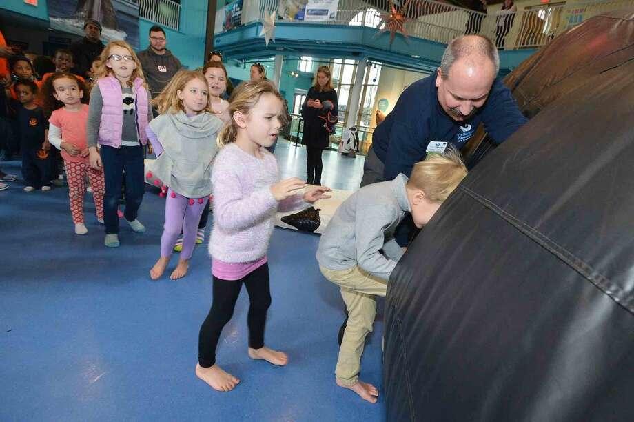 Hour Photo/Alex von Kleydorff Marketing Director Chris Loynd lets kids inside the 40 foot inflatable Hunchback Whale
