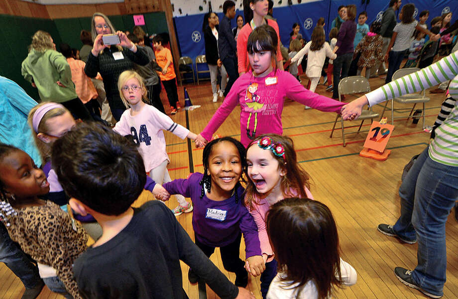Hour photo / Erik Trautmann Kindergartners, Madison Santos-Perkins and Caitlin Dudek, center, circle while holding hands as part of the Columbus Magnet School annual All School Meeting Peace Games assembly that honors the work and memory of Dr. Martin Luther King, Jr.
