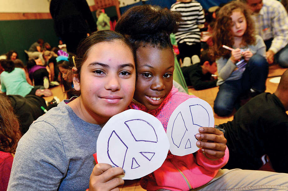 Hour photo / Erik Trautmann 5th graders Julissa Acosta and Mecca Richards hold their peace craft during the Columbus Magnet School annual All School Meeting Peace Games assembly that honors the work and memory of Dr. Martin Luther King, Jr.