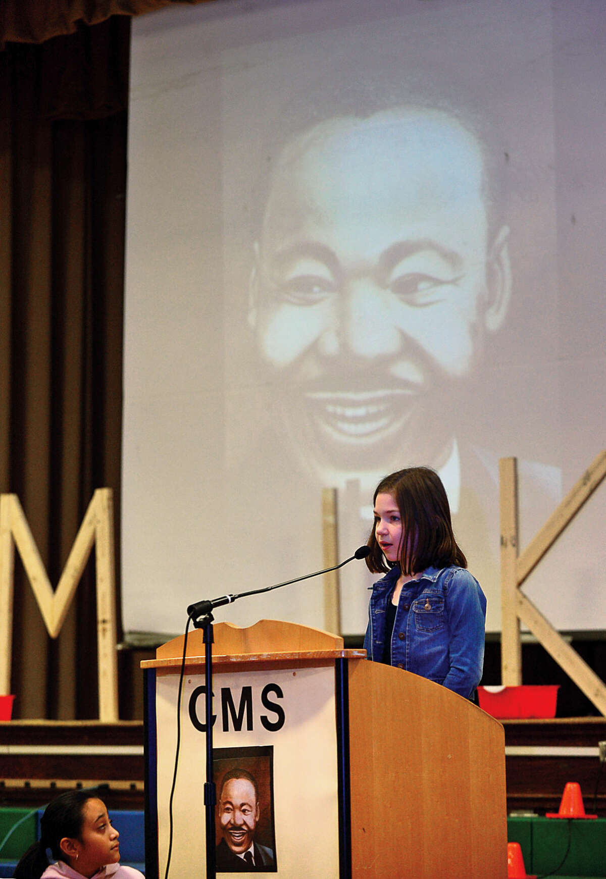 Hour photo / Erik Trautmann 3rd grader Katie Romano reads a letter she wrote to the late Dr. Martin Luther King Jr. as part of the Columbus Magnet School annual All School Meeting Peace Games assembly that honors the work and memory of Dr. King.
