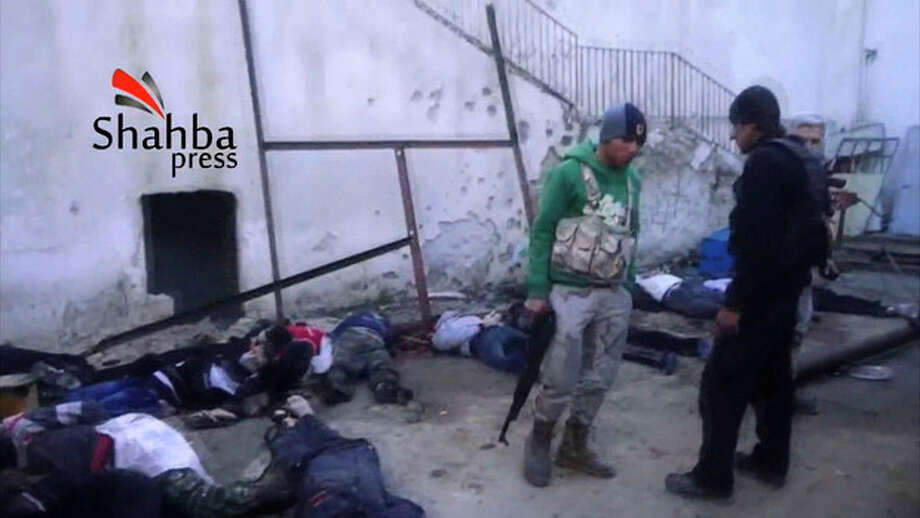 This image made from citizen journalist video posted by the Shahba Press on Wednesday, Jan. 8, 2014, which has been verified and is consistent with other AP reporting, shows rebel fighters standing next to dead bodies after they ousted Islamic State of Iraq and the Levant (ISIL) from their headquarters in an Aleppo, Syria hospital. Activists said the people were killed by ISIL, an al-Qaida affiliate trying to build Islamic rule across Syria. Rebel-on-rebel fighting between an al-Qaida-linked group and an array of more moderate and ultraconservative Islamists has killed nearly 500 people over the past week in northern Syria, an activist group said Friday, in the most serious bout of violence among opponents of President Bashar Assad since the civil war began.(AP Photo/Shahba Press via AP video) / Shahba Press